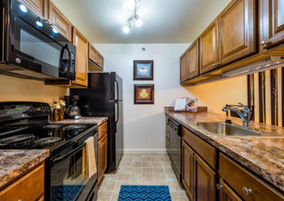 Large kitchen with granite countertop and wooden cabinets in The Meadows apartment