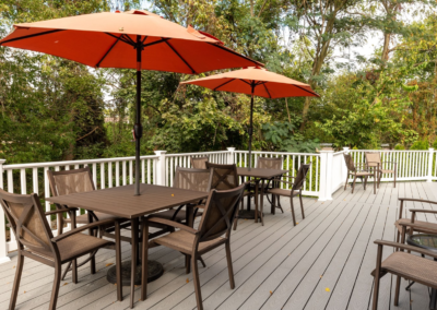 Comfortable seating area with parasols outside of The Meadows clubhouse for apartment residents in Lehigh Valley, PA